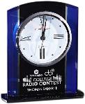 Black and Blue Glass Clock. A large clock with Roman numbers is embedded in an arched top design with black glass center with royal blue sides. Your personalization is included